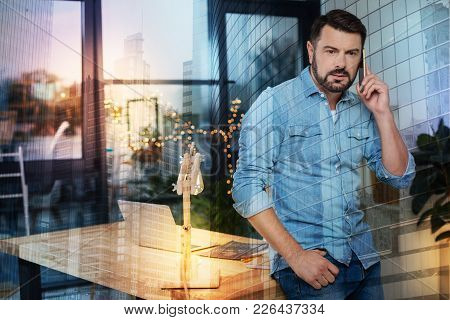 Phone Talk. Young Attentive Man Looking Serious While Standing Near The Table In His Comfortable Lac