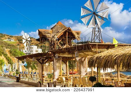 Decorative Windmill With White Propeller Installed On Thatched Roof. Tables With Thatched Umbrellas