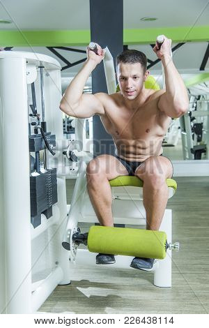 Young Bodybuilder Working Out In Gym, Doing Ab Exercise Crunches Using A Machine
