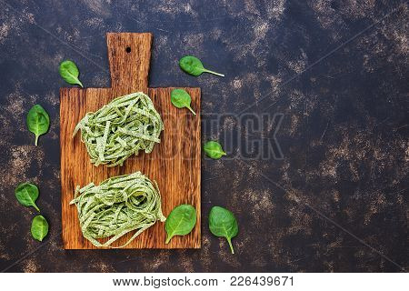 Raw Green Pasta With Spinach On A Cutting Board, On A Dark Blue Background