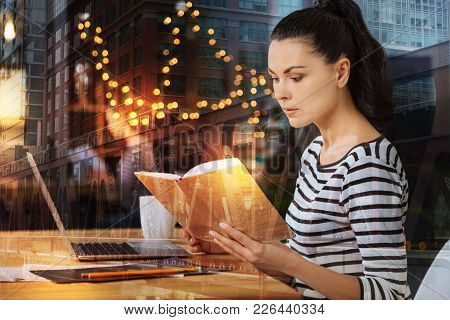 How Interesting. Calm Attentive Young Woman Sitting At The Table With A Modern Laptop On It And Feel