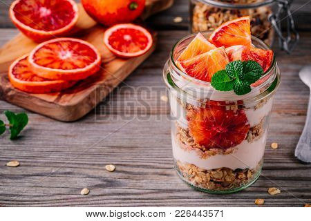 Healthy Breakfast  Glass Jar Yoghurt Parfait With Homemade Granola And Blood Orange On A Wooden Back