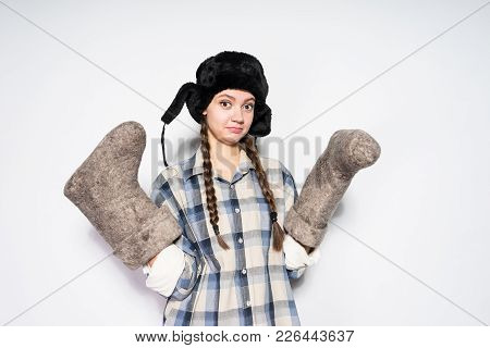 Funny Young Russian Girl In A Black Hat With Ear-flaps Holds Gray Felt Boots In Her Hands
