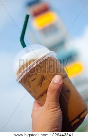 Iced Coffee In Plastic Glass With Amusement Park Background