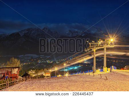 Long Illuminated Ski Slope At Night With Snow Capped High Tatra Mountains On Background, Zakopane, P