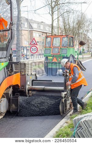 Laan Van Meerdervoort, The Hague, The Netherlands - 31 March 2017: Road Work Team Laying Blacktop To