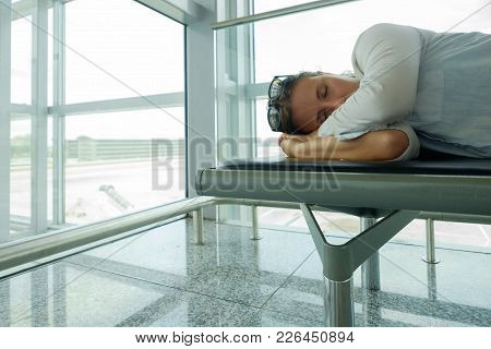Delayed Aeroplane Concept. Tired Passenger Is Sleeping In Airport Terminal And Waiting For Airplane