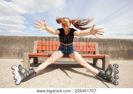 Happy Joyful Young Woman Wearing Roller Skates Relaxing After Long Ride. Girl Having Fun During Summ