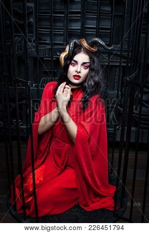 Beautiful Woman In A Red Dress Is Sitting On Her Lap In A Cage. She Has A Serpent On Her Horns