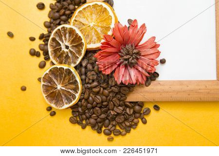 Wooden Photo Frame On The Table With A Red Flower, Orange Slices And Scattered Coffee Beans, Top Vie
