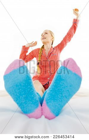 Sleepwear Fashion And Accessories Concept. Woman In Pajamas Wearing Furry Warm Socks Relaxing On Bed