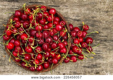Basket With Red Sweet Cherry Fruits On Vintage Wooden Table. Summer Fruit Season Concept