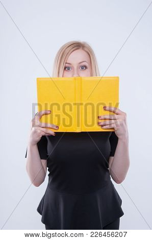 Surprised And Amazed Business Woman In Black Dress Peeps Out From A Notepad. Young Attractive Blond