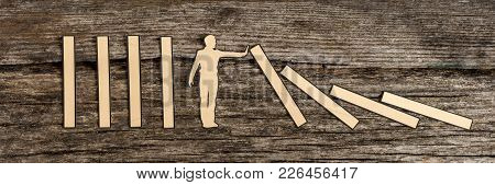 Man Stopping The Domino Effect In A Conceptual Image Of A Paper Cutout Silhouette On A Rustic Wood B