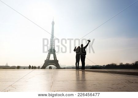 Couple At Eiffel Tower. Travelers And Tourists Exploring The World And The City Of Paris. Romantic L