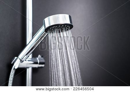 Water Running From Shower Head In Bathroom With Dark Black Background. Simple Stylish And Modern Sca