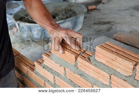 Bricklayer Worker Installing Bricks On Construction Site