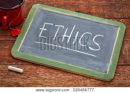 ethics word - white chalk handwriting on a slate blackboard with a cup of tea
