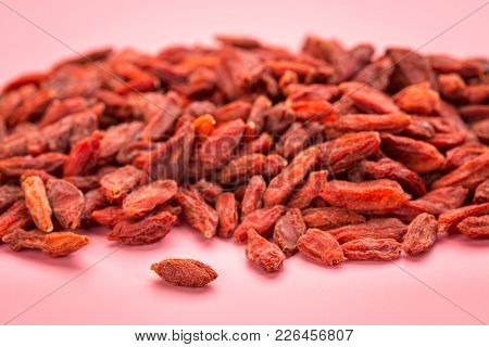 pile of dried red Tibetan goji berries (wolfberry) on a pink background