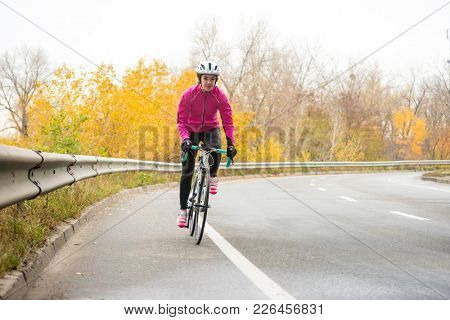 Young Woman in Bright Pink Jacket Riding Road Bicycle on the Highway in the Cold Autumn Day. Healthy Lifestyle Concept.