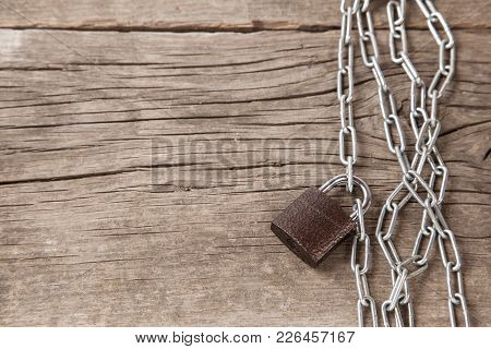 Closed Lock With A Chain Lies On An Old Wooden Table. Copy Space For Text