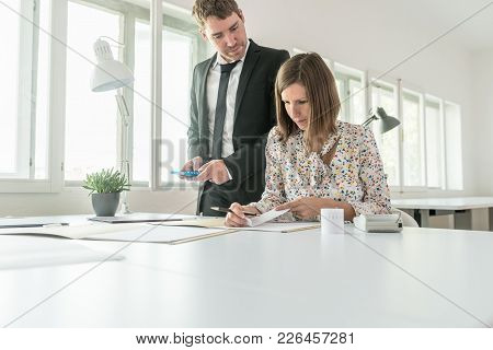 Tax And Accounting Concept - Female And Male Accountant Calculating Costs And Expenses Using Calcula