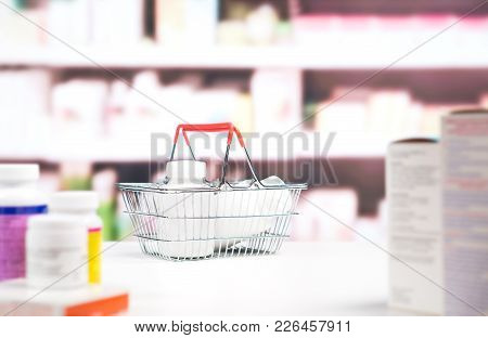 Pharmacy With Medication And Shelves. Shopping Basket Full Of Medicine And Pill Bottles On The Count