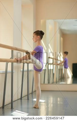 Girl Stretching Out In Ballet Studio. Young Ballet-dancer Standing At Railing With Raised Leg. Flexi