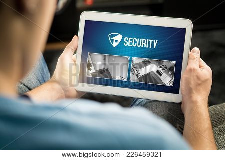 Man Using Home Security System And Application In Tablet. Watching Protection Camera Live Footage In