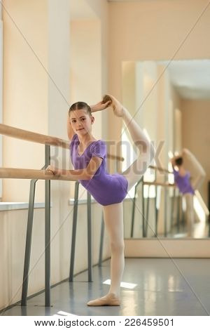 Young Ballerina Doing Exercise. Beautiful Young Ballerina Making A Stretching Before Dance. Work And