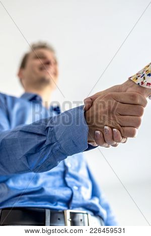 Businessman In Blue Shirt Shaking Hands With A Woman In A Low Angle View.
