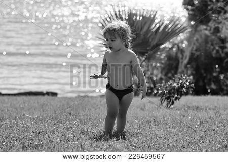 Cute Surprised Baby Boy With Blond Hair In Red Trunks Walks On Green Grass Outdoors On Idyllic, Sunn