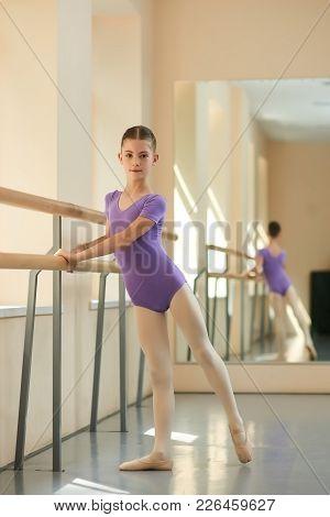 Young Attractive Ballerina Near Barre. Beautiful Girl Standing Near Railing In Ballet Class. Workout