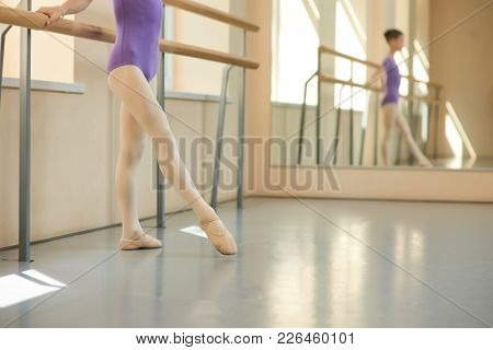 Young Ballerina In Ballet Hall, Cropped Image. Girl Standing Near Barre In Ballet Studio In Ballet S