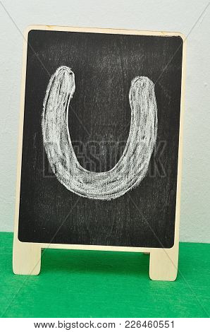 A Black Board With A Horse Shoe Drawn On To It