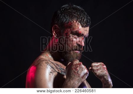 Power, Might, Magic. Man In Fight Position With Blood Paint On Face, Fists. Sport, Boxing, Fighting.