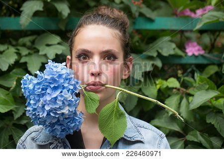 Girl With Makeup Face Hold Blue Hydrangea In Mouth. Young Woman With Surprised Look And Flower. Skin