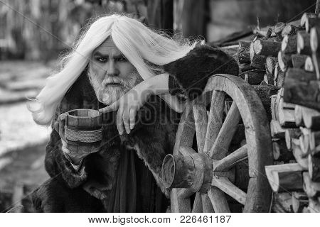 Druid Old Bearded Man With Long Grey Hair And Beard In Fur Coat With Wooden Mug In Hands Near Wheel