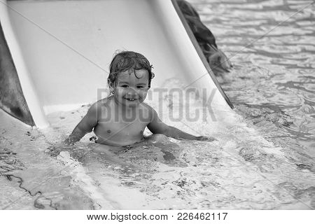 Cute Happy Baby Boy With Wet Blond Hair Rides From Waterslide In Pool Water Or Aqua Park Outdoors On
