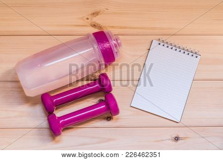 Two Pink Dumbells, Notebook And Water Bottle On Wooden Background. Fitness And Health.