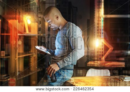 Looking Interested. Serious Young Attentive Man Looking At The Screen Of His Modern Tablet While Sit