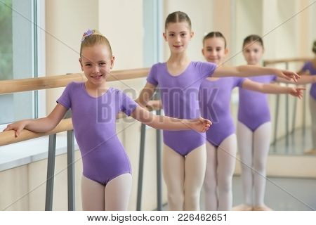 Kids Practicing Ballet At Ballet Class. Young Smiling Ballerina Standing In Pose At Ballet Barre.