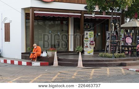 Chiang Mai,  Thailand - January 29 2018; Monk In Saffron Robes Wearing Surgical Face Mask With Plast