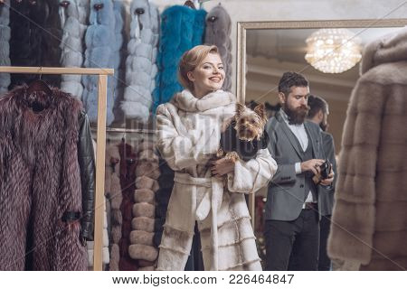 Fashion And Beauty, Winter. Fashion, Woman With Yorkshire Terrier Pet Dog And Man Buy Fur Coat.