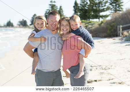 Young Happy Beautiful Caucasian Family Having Holidays On The Beach Smiling With Mother And Father C