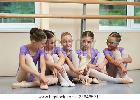Young Ballerina With New Ballet Slippers. Group Of Young Ballet Dancers Sitting On Floor During A Br