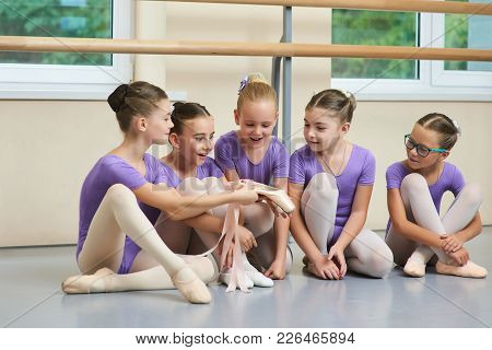 Excited Young Ballerinas Looking On New Slippers. Beautiful Young Ballerina Showing New Ballet Shoes