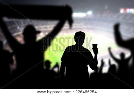 Football Fan Drinking Beer In Crowd In Stadium. Man With Alcohol Beverage In Soccer Audience At A Ga