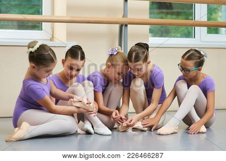 Young Ballerinas At Classical Dance School. Young Beautiful Ballet Dancers Sitting On The Floor. Kid