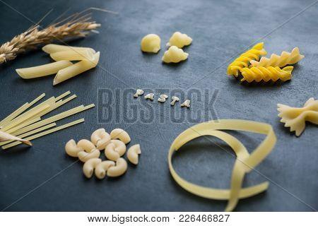 Several Types Of Pasta Lie On A Dark Wooden Board